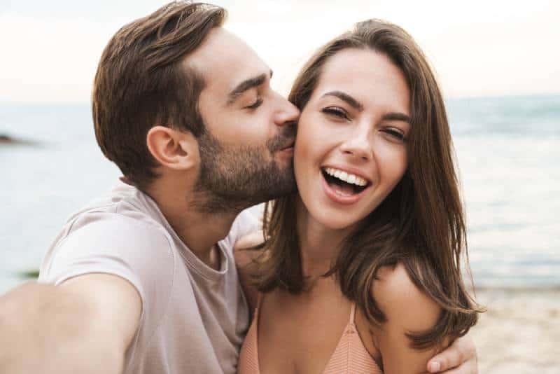 homme embrassant une femme souriante sur la joue tout en prenant une photo