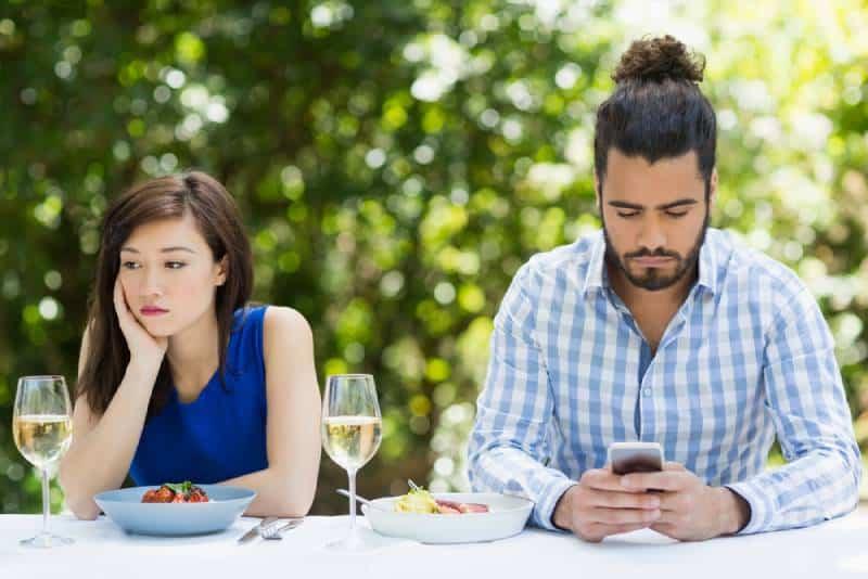 homme ignorant sa petite amie et utilisant le téléphone