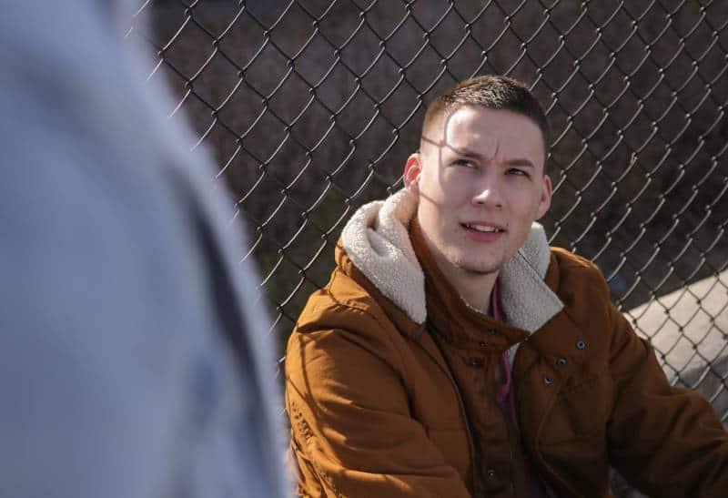 homme portant une veste marron, assis près d'une clôture