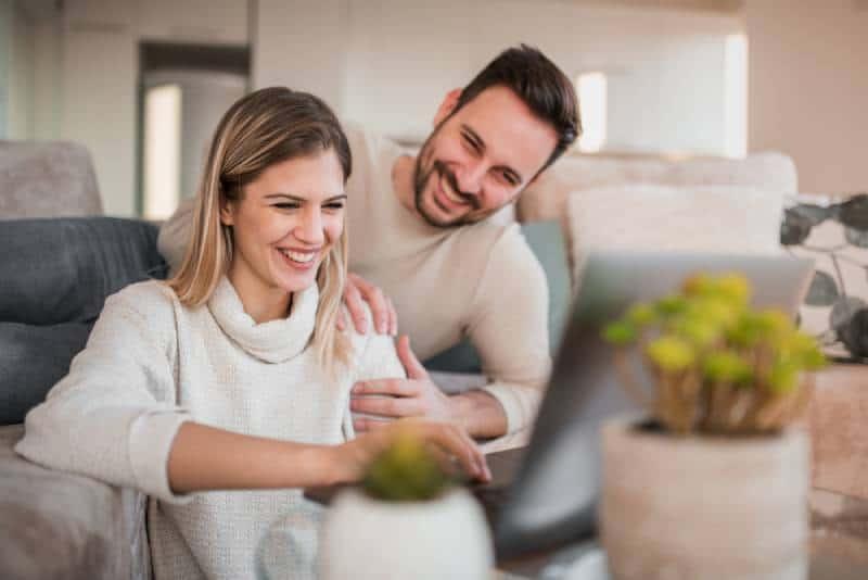 jeune couple heureux assis dans le salon et tapant sur son ordinateur portable