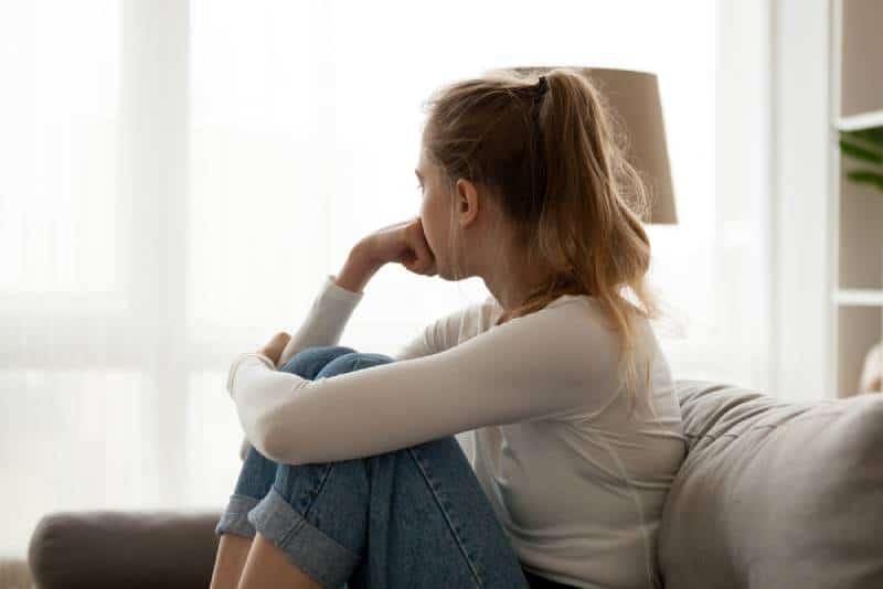 jeune femme à l'air pensif et regardant au dehors