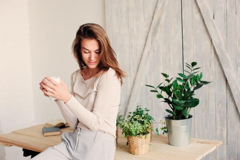 jeune femme se détendant à la maison avec une tasse de café