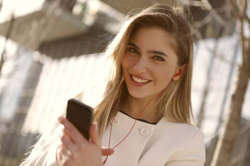 portrait d'une jeune fille souriante qui tape sur son téléphone