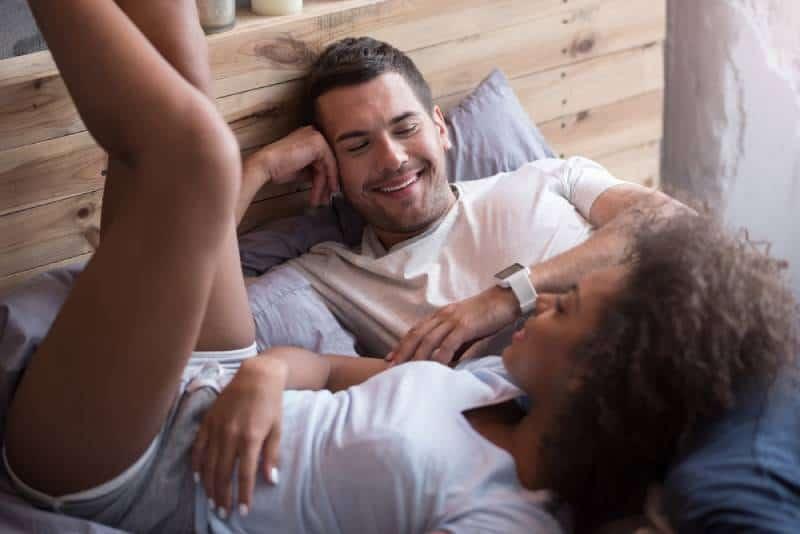 un couple heureux allongé sur le lit et qui parle