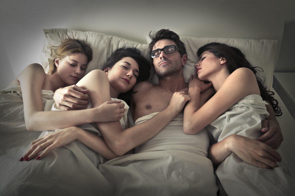 un homme dort avec trois femmes