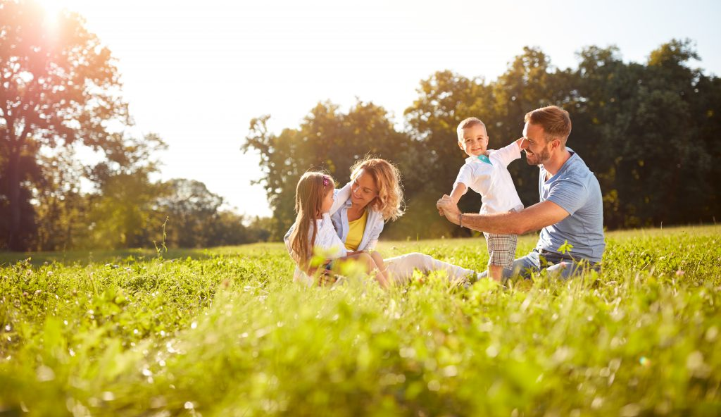 un homme et une femme avec des enfants dans un pré