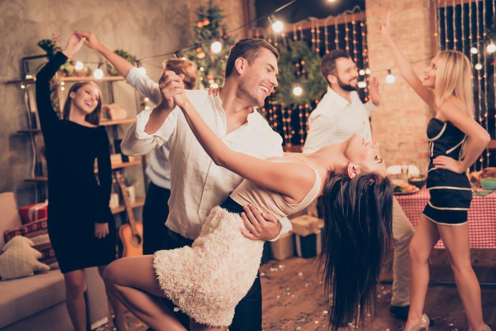 un homme et une femme dansant en compagnie d'amis
