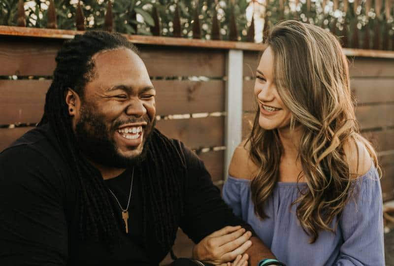 un homme et une femme souriant à l'extérieur