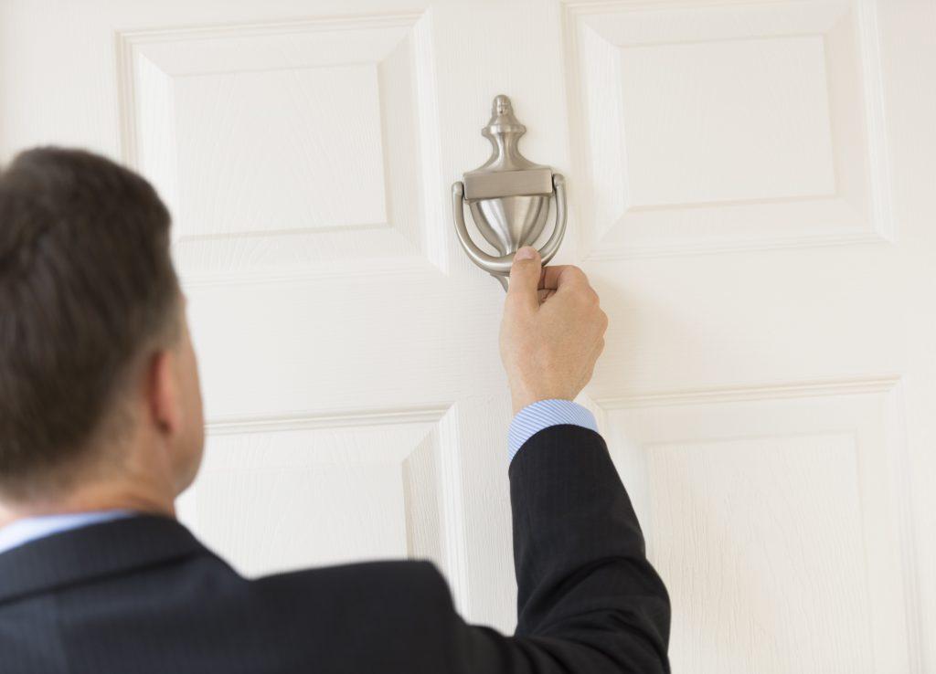 un homme frappe à la porte