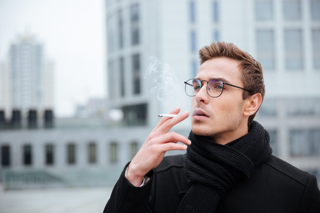 un homme fume une cigarette