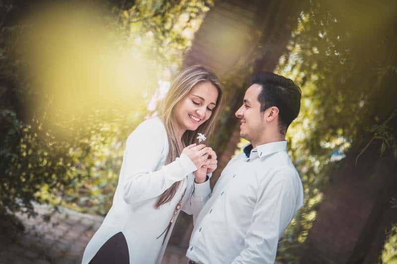 un homme offre une fleur blanche à une femme entourée d'arbres verts