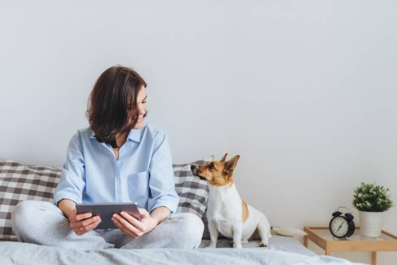 une femme en pyjama est assise sur le lit dans la chambre à coucher avec son chien