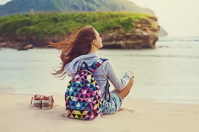 une femme heureuse assise sur la plage
