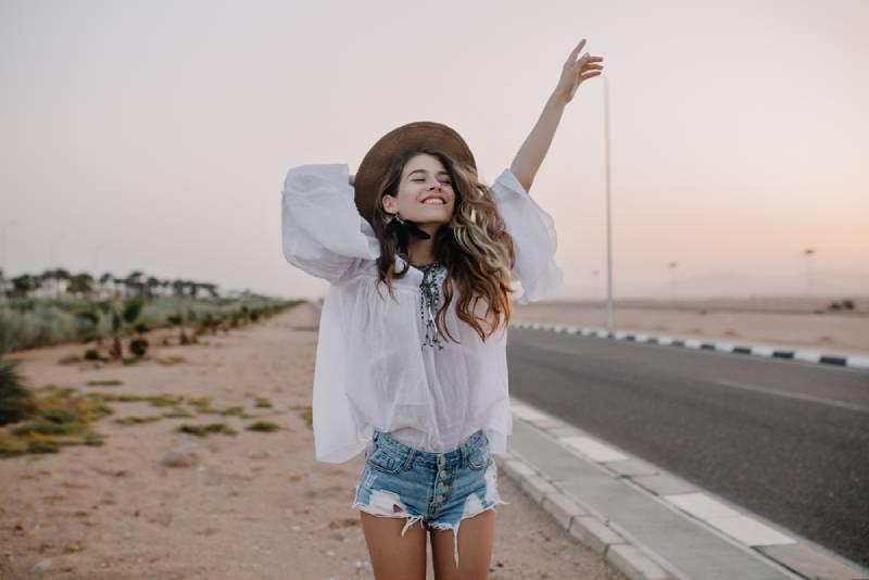 une femme heureuse qui marche et qui lève la main à l'extérieur