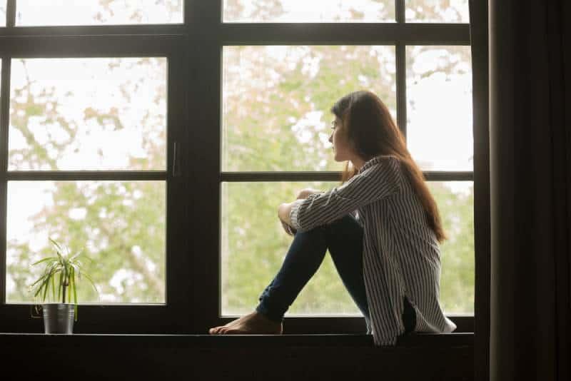une femme réfléchie, assise près de la fenêtre de sa maison