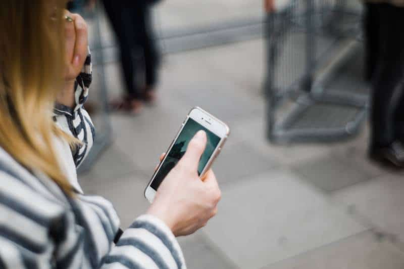 une fille qui tape un téléphone à l'extérieur