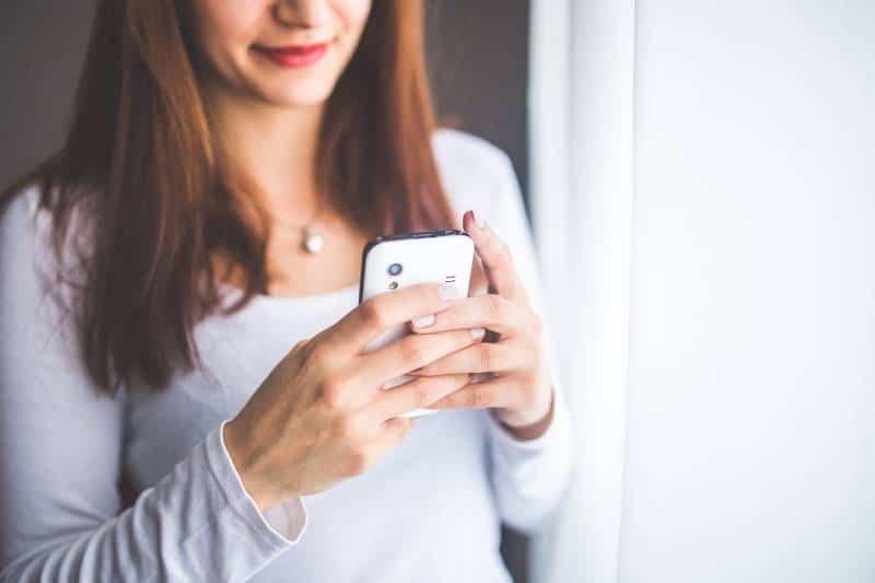 une fille souriante tape des sms à la maison