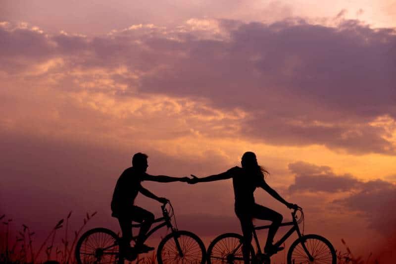 silhouette d'homme et femme, faire du vélo et essayer de toucher leurs mains