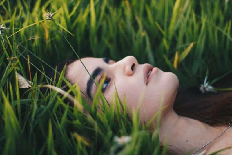photographie de portrait d'une femme allongée sur l'herbe