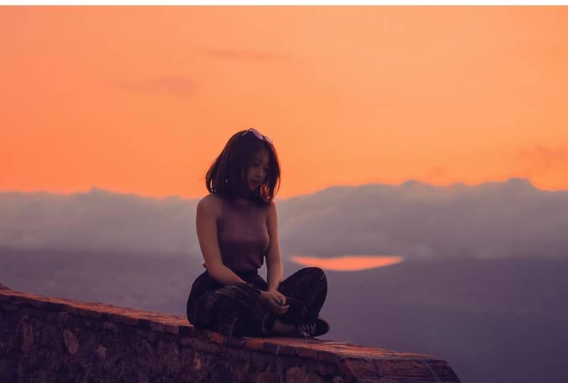 Femme assise sur une falaise