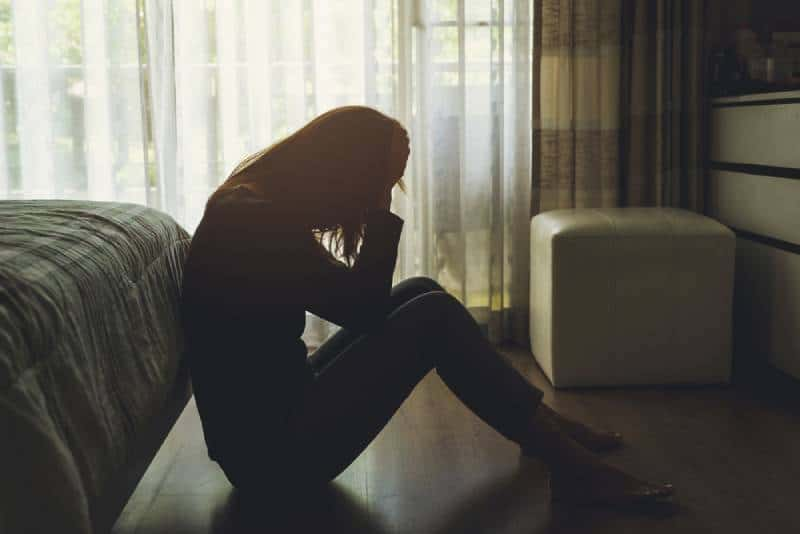 Jeune femme solitaire assise, la tête déprimée dans les mains, dans la chambre sombre