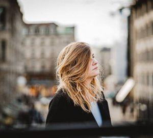 femme en manteau noir se tenant près d'un bâtiment pendant la journée