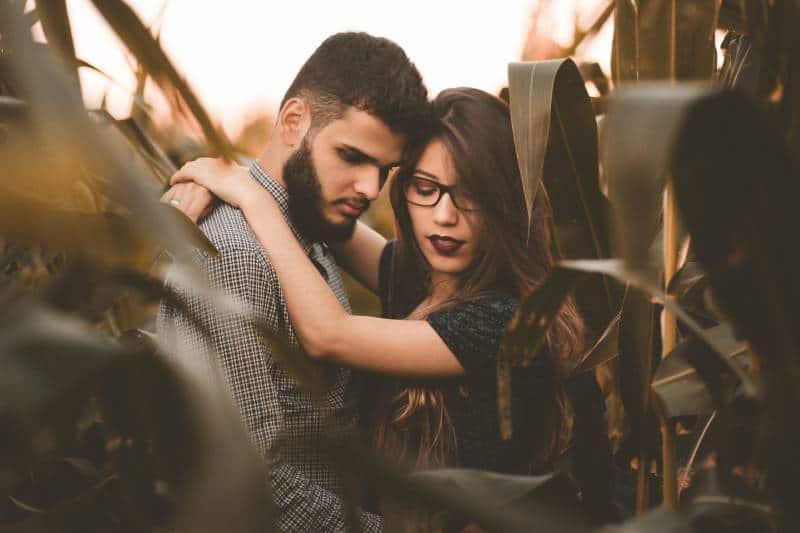 Un couple s'embrassant dans un champ de maïs