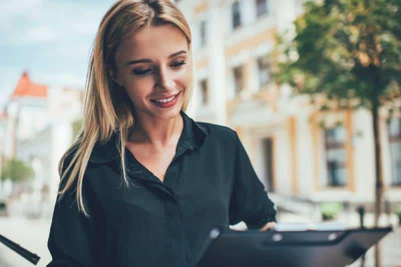 Une femme heureuse en tenue décontractée analyse les informations contenues dans les journaux