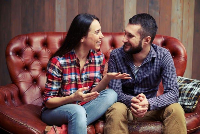 couple heureux parler assis côte à côte sur un canapé rouge