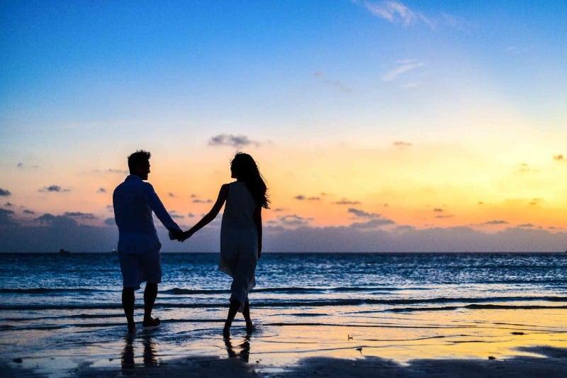 homme et main dans la main marchant sur le bord de mer au moment du coucher du soleil bord de mer