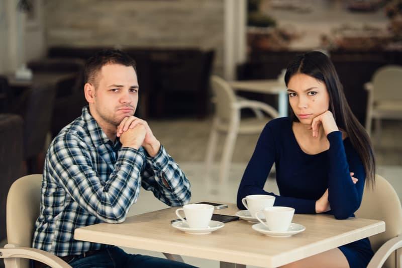 couple sérieux assis au café