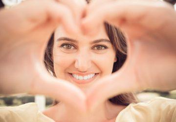 fille heureuse en forme de coeur avec ses mains
