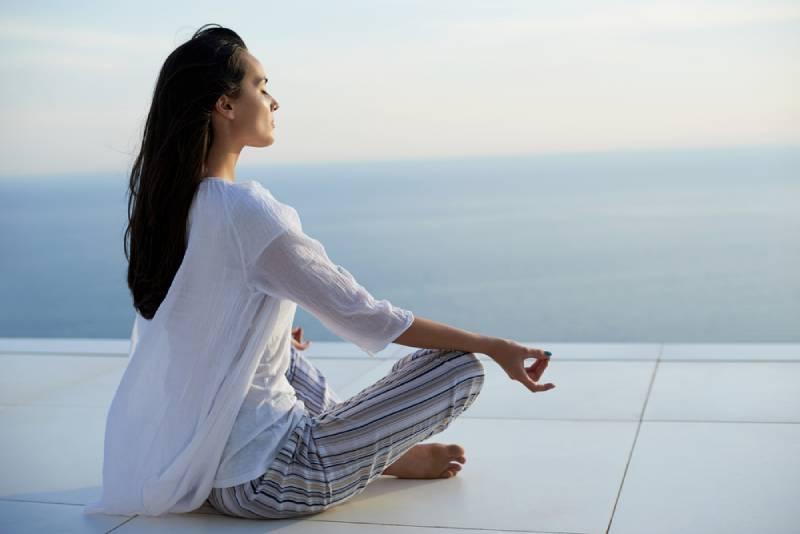 des jeunes femmes pratiquent la méditation yoga au coucher du soleil avec vue sur la mer en arrière-plan