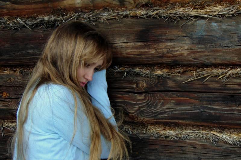 femme appuyée sur un mur de bois noir