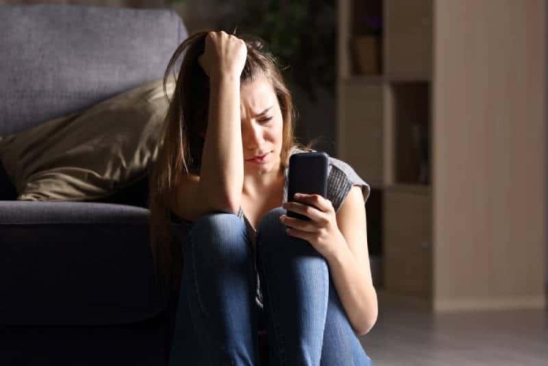 femme dépressive regardant son téléphone