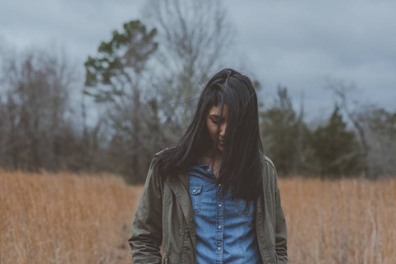 femme portant un cardigan gris entouré d'herbe
