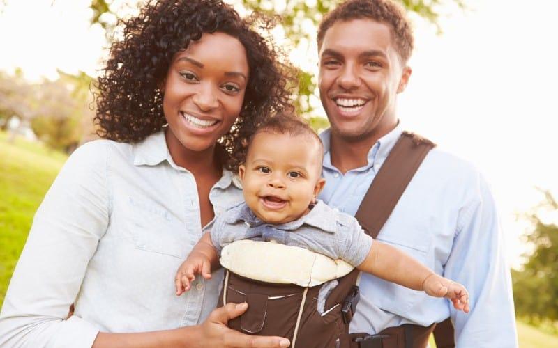 homme et femme avec bébé dans un porte-bébé
