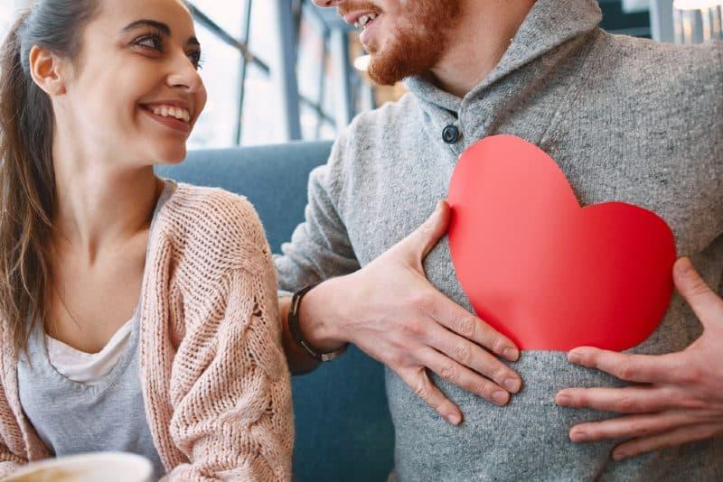 Un homme tenant un coeur rouge devant une femme heureuse