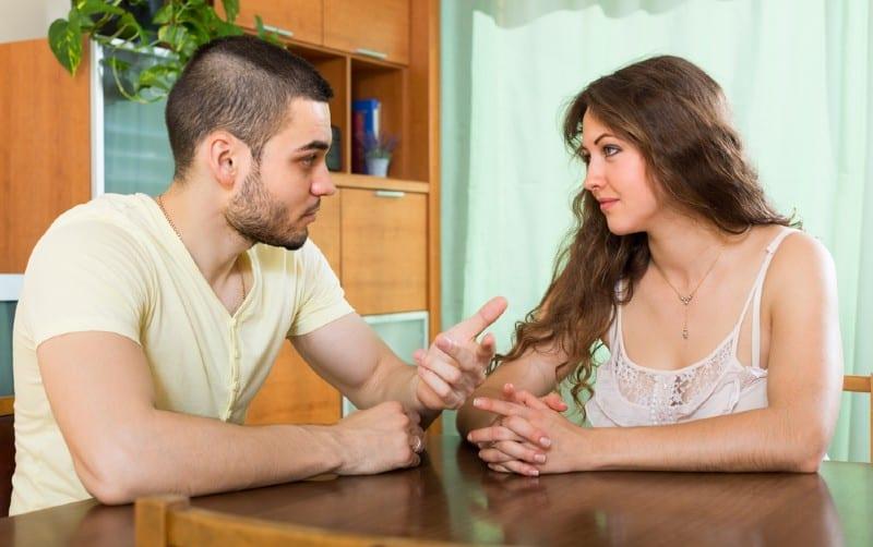 Jeune couple assis à une table et de parler