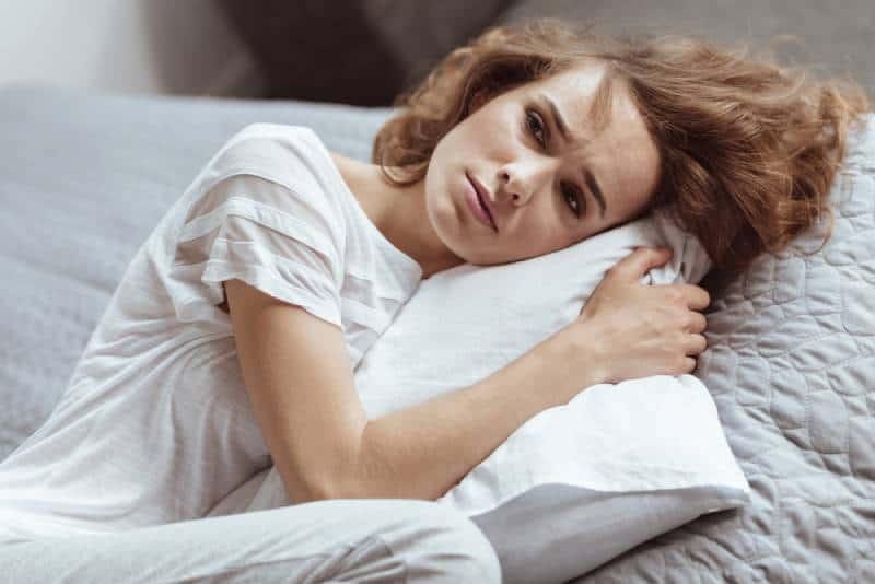 mature allongé sur un oreiller et pensant à quelque chose de déprimant à la maison