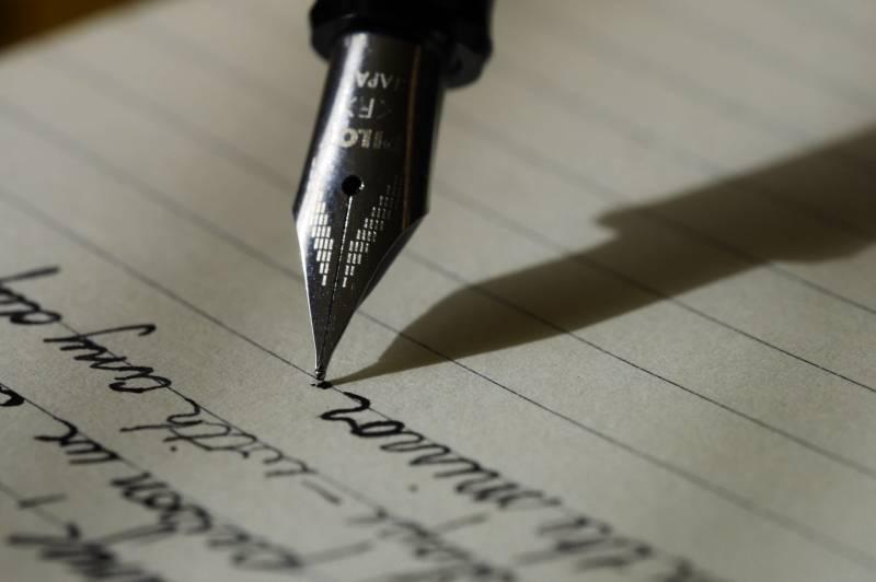 stylo plume sur papier ligné noir
