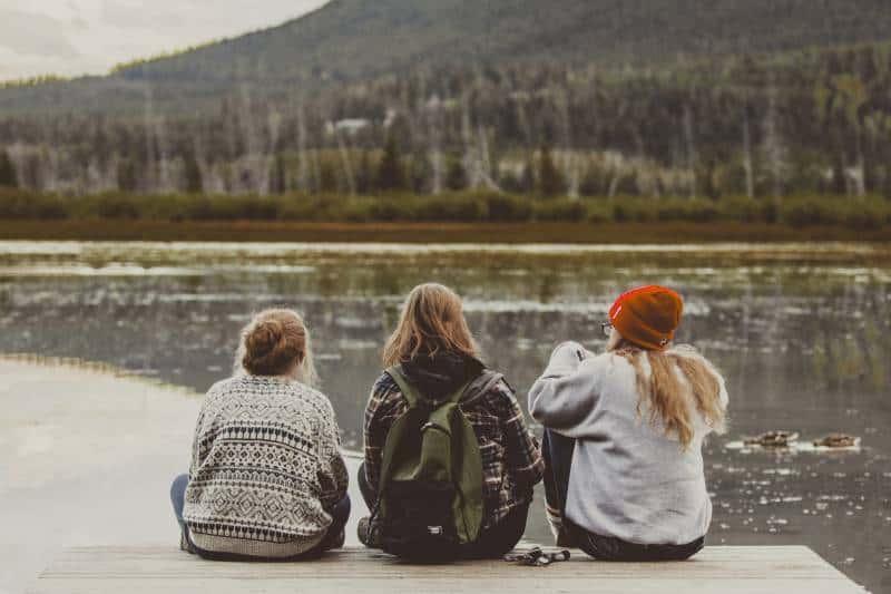 trois amies assises au bord du lac