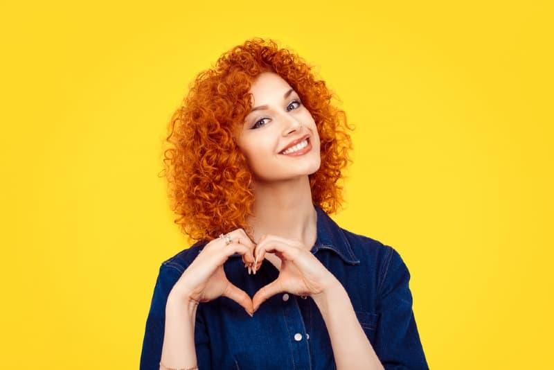 une femme faisant signe de coeur avec ses mains