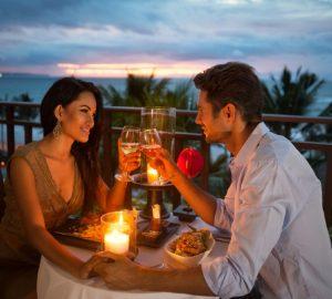 un homme et une femme assis à une table ayant un rendez-vous romantique