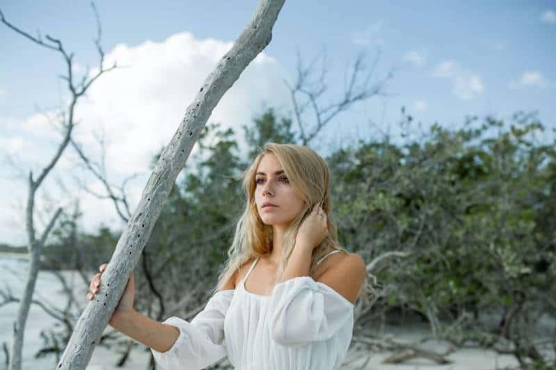 jeune femme blonde portant une robe blanche et se tenant dehors près d'un arbre