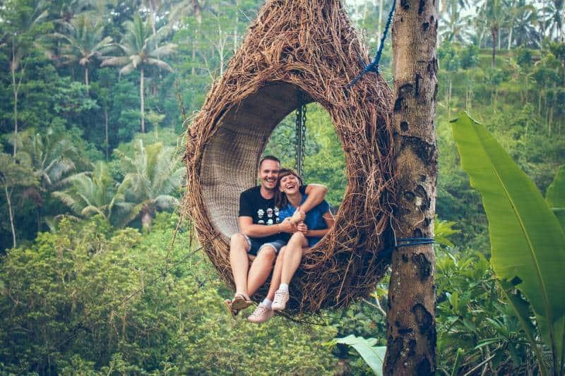 Un homme et une femme souriants sur un hamac brun à côté des arbres