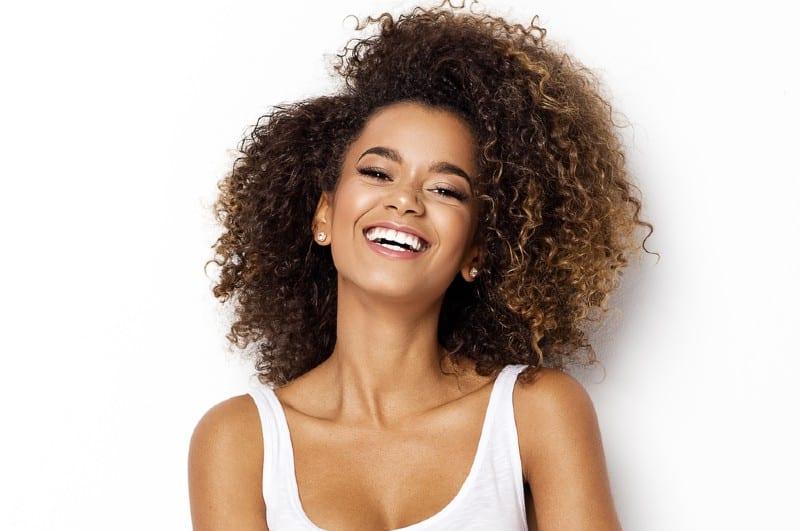 Belle fille afro-américaine avec une coiffure afro souriant