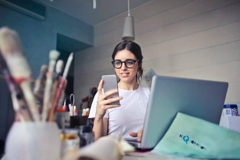 femme assise à une table et en appuyant sur un téléphone