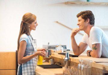 Vue latérale d'un jeune homme et d'une jeune femme flirtant dans un café