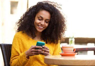 femme afro portant un sweatshirt jaune et tapant sur son téléphone